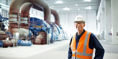 Close up picture of an engineer in front of a turbine in power plant