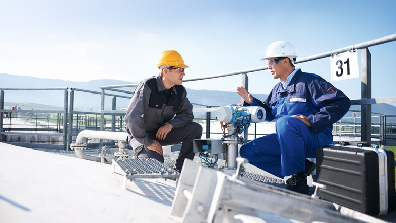 Customer and Endress+Hauser engineer discussing on the top of a tank.